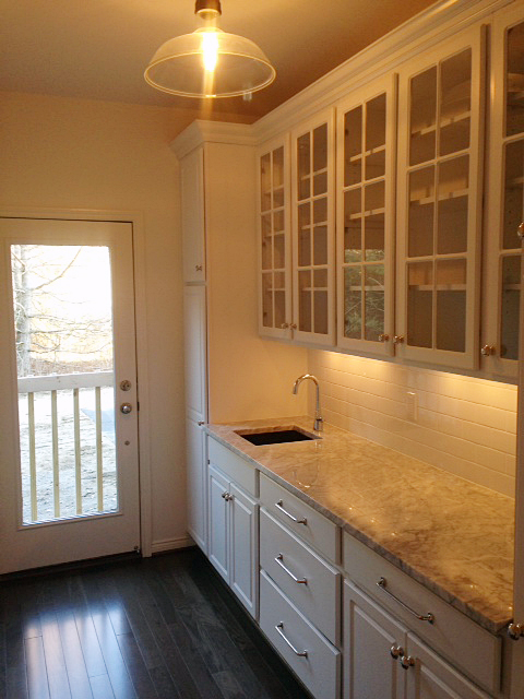 Butler pantry with sink and subway tile backsplash and indirect lighting under cabinets