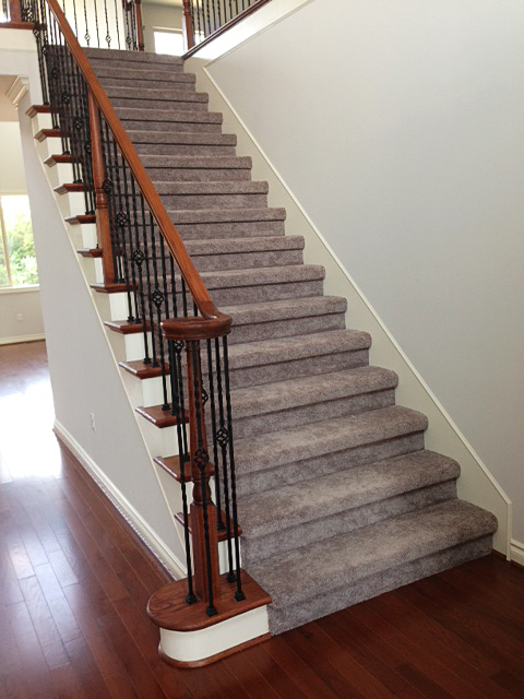 Carpeted staircase with over-the-top handrail and rod iron basket spindles