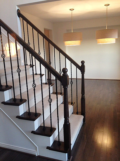 Carpeted staircase with wooden end caps