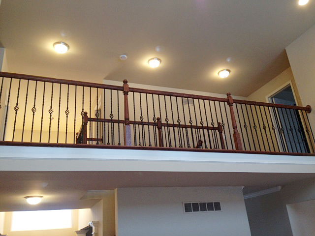 Catwalk with railing featuring rod iron basket spindles