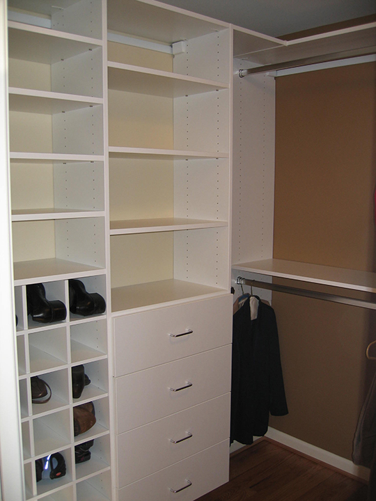 Closet with white painted custom shelving and drawers