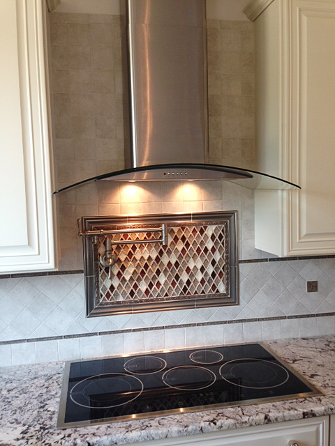 Cook top with tile back splash, pot filler, and stainless steel-glass hood vent
