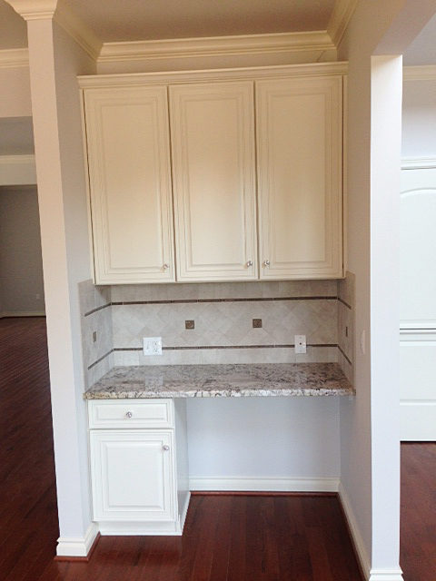 Desk area adjacent to kitchen with matching cabinetry