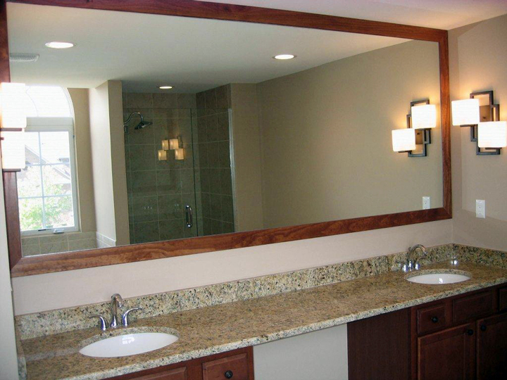 Dual sink bathroom with a stained framed mirror