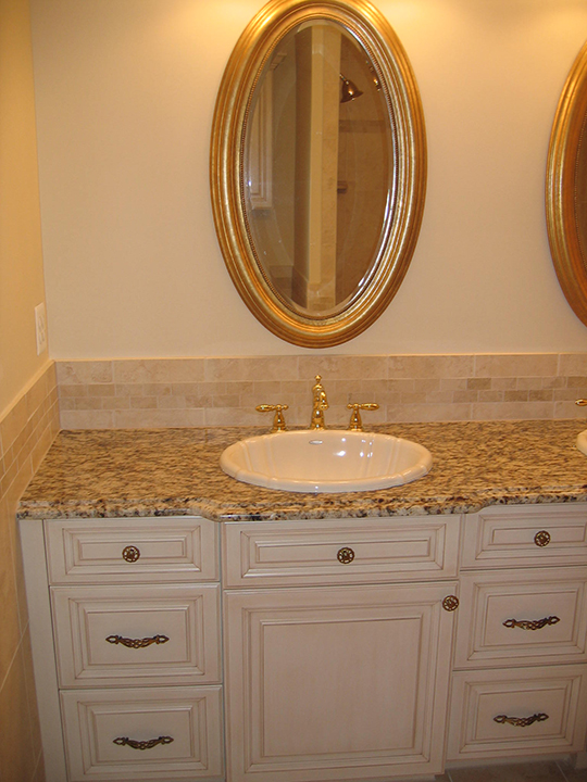 Dual vanity with tile backsplash, granite counter tops and painted cabinets