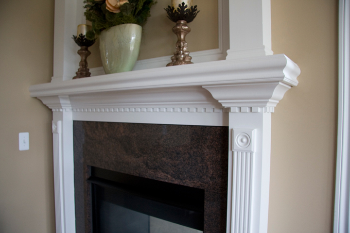 Fireplace surrounded in granite tile with white painted mantle