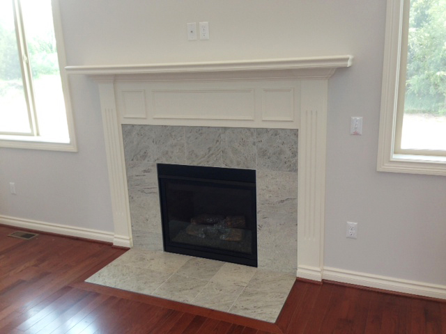 Fireplace surrounding by granite tile and painted mantle above