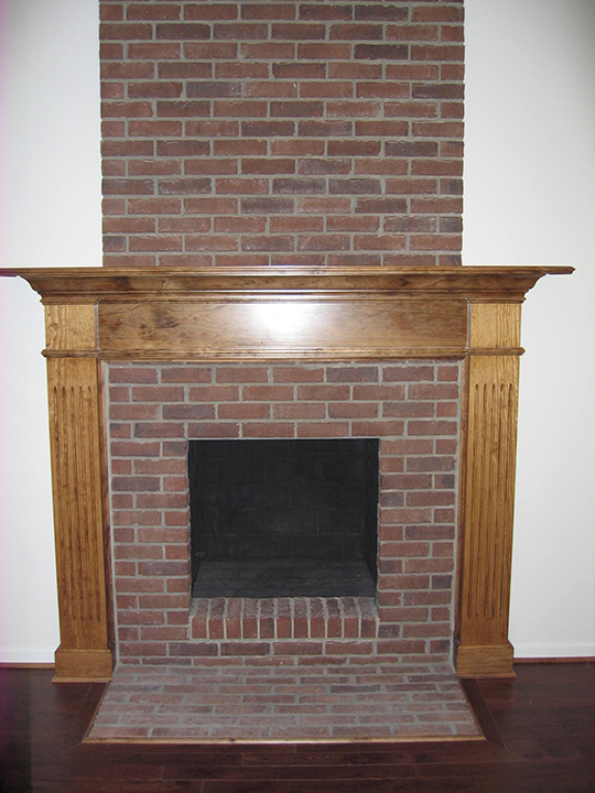 Fireplace with brick landing and wooden mantle