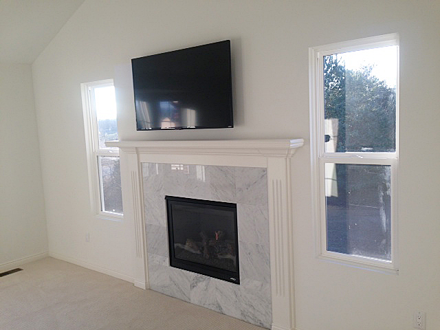 Fireplace with tv hung above the white painted mantle