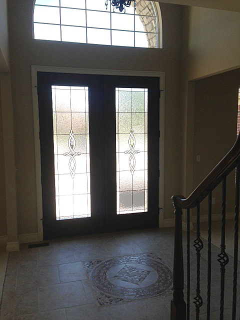 Foyer with frosted glass front door and medalion inlay on floor