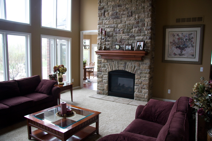 Great room with two story windows and stone fireplace