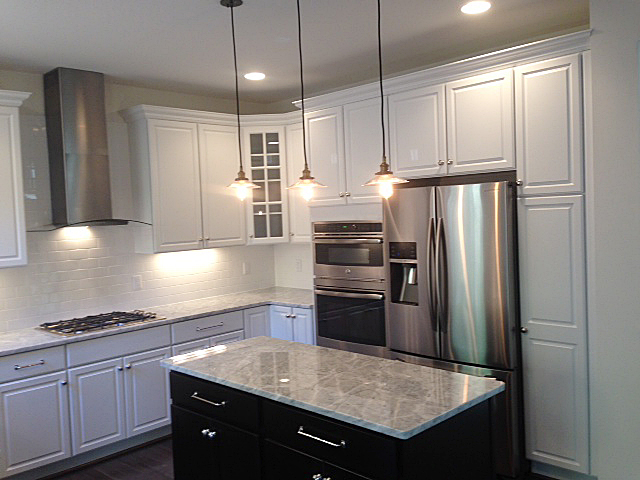 Kitchen featuring island with contrasting cabinet color