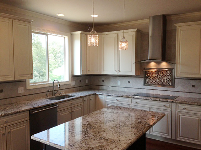 Kitchen featuring white painted cabinets, granite counter tops, stainless hood vent and pot filler