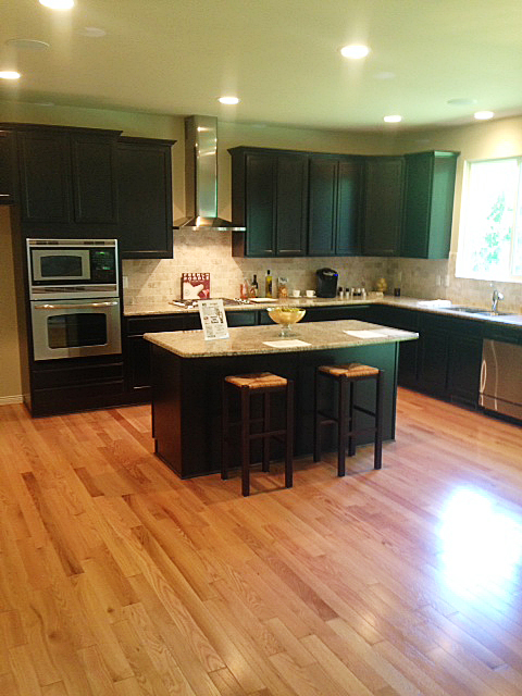 Kitchen with dark mocha cabinets and island with snack bar overhang
