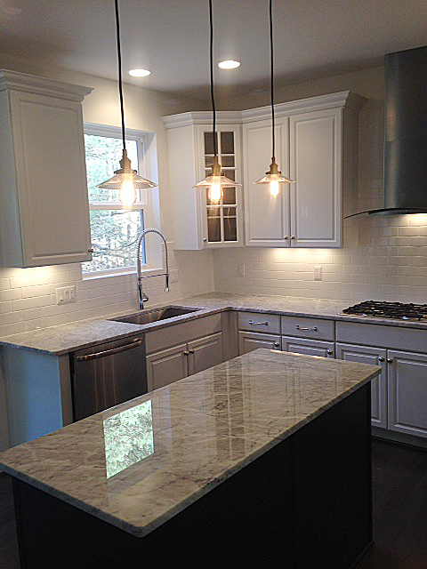 Kitchen with subway tile back splash and white painted cabinets