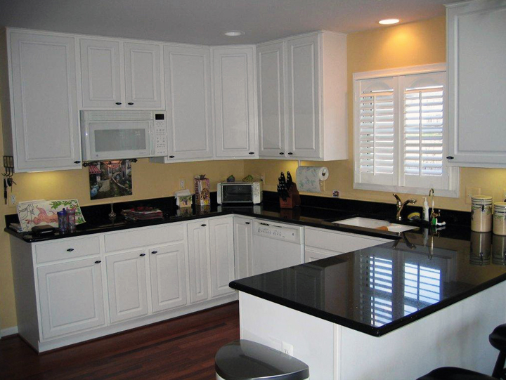 Kitchen with white painted cabinet and dark quartz countertops