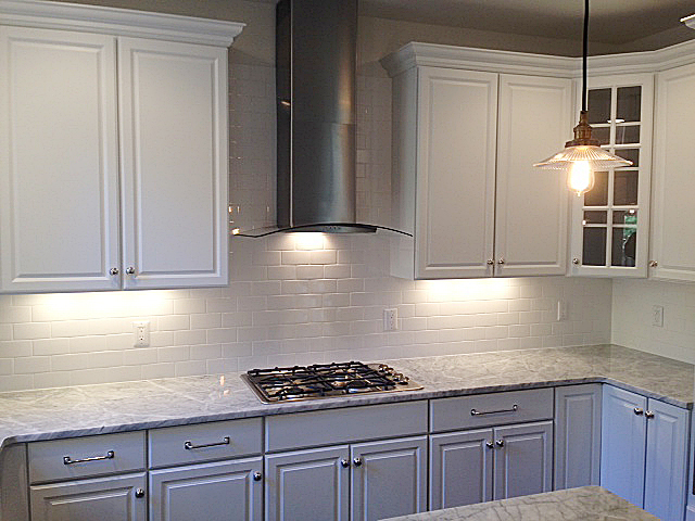 Kitchen with white painted cabinets, granite counter tops, cook top and stainless steel range hood