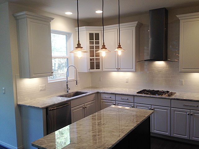 Kitchen with white painted cabinets, subway tile back splash and contrasting color island