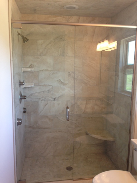 Master bath shower with Euro doors, marble bench, and body sprayers