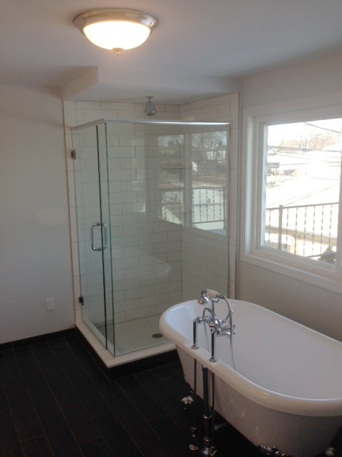 Master bath with free standing tub next to shower with euro style door