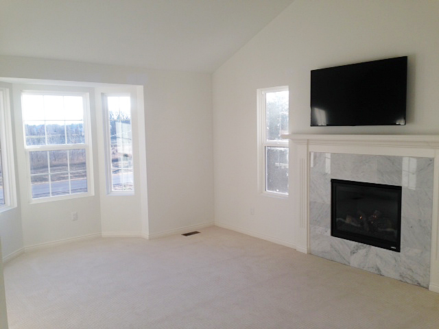 Master bedroom with tile surrounded fireplace and tv over mantel