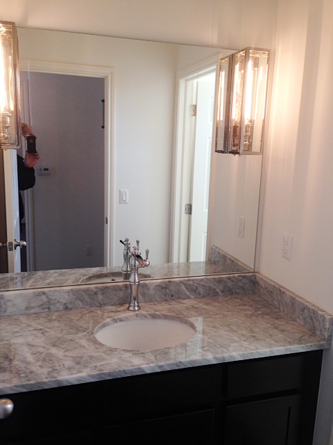 Powder room with mirror featuring built in light sconces