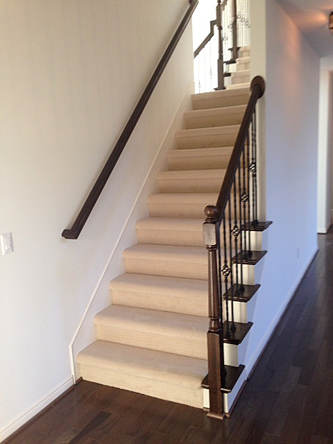Split staircase with carpeted with wooden end caps