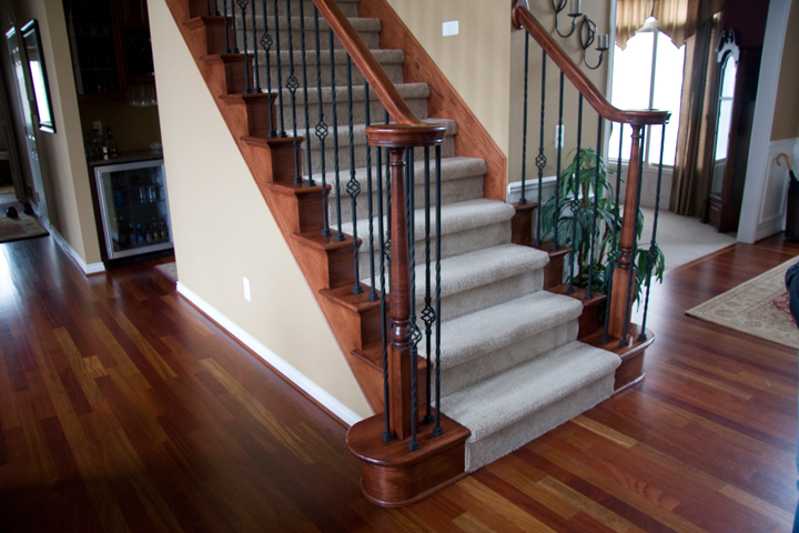 Staircase with maple railing and rod iron spindles with decorative baskets