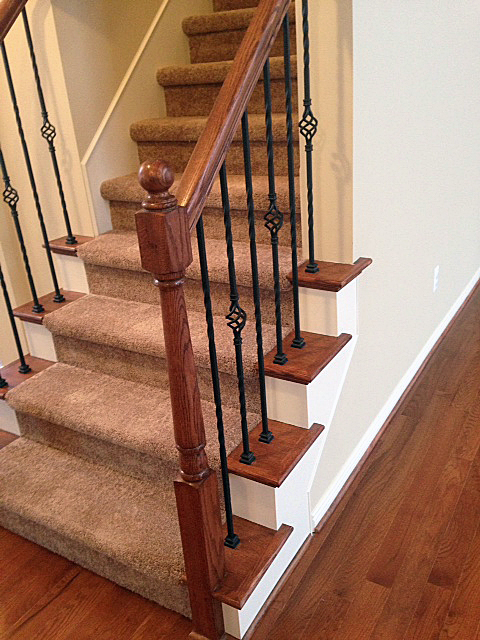 Staircase with oak end caps and rod iron basket spindles