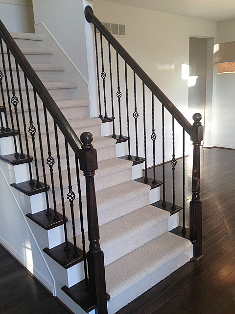 Stairway with dark stained wooden railing, rod iron spindles with baskets, and wooden end caps