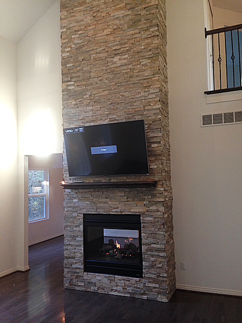 Two room fireplace with stacked ledge rock from floor to ceiling