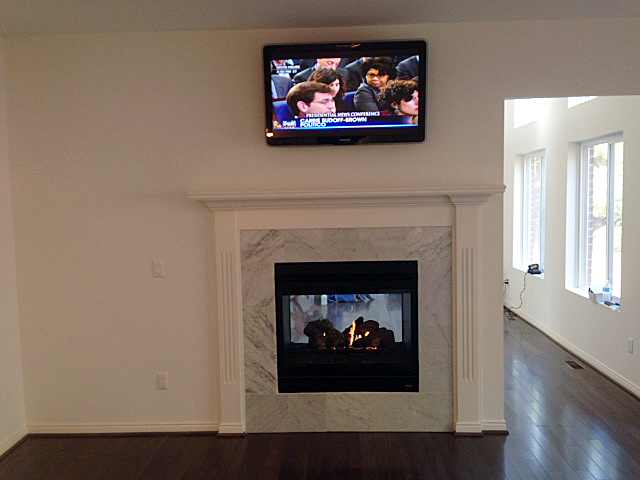 Two sided fireplace between kitchen and great room, encased in tile