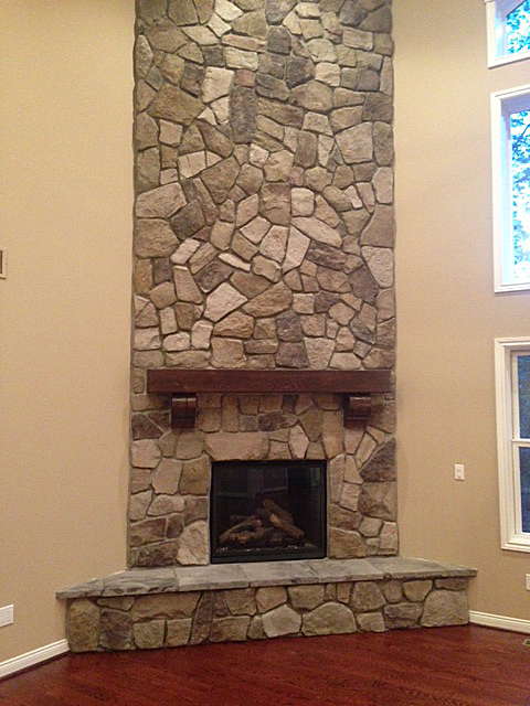 Two story stone fire place with wooden mantel