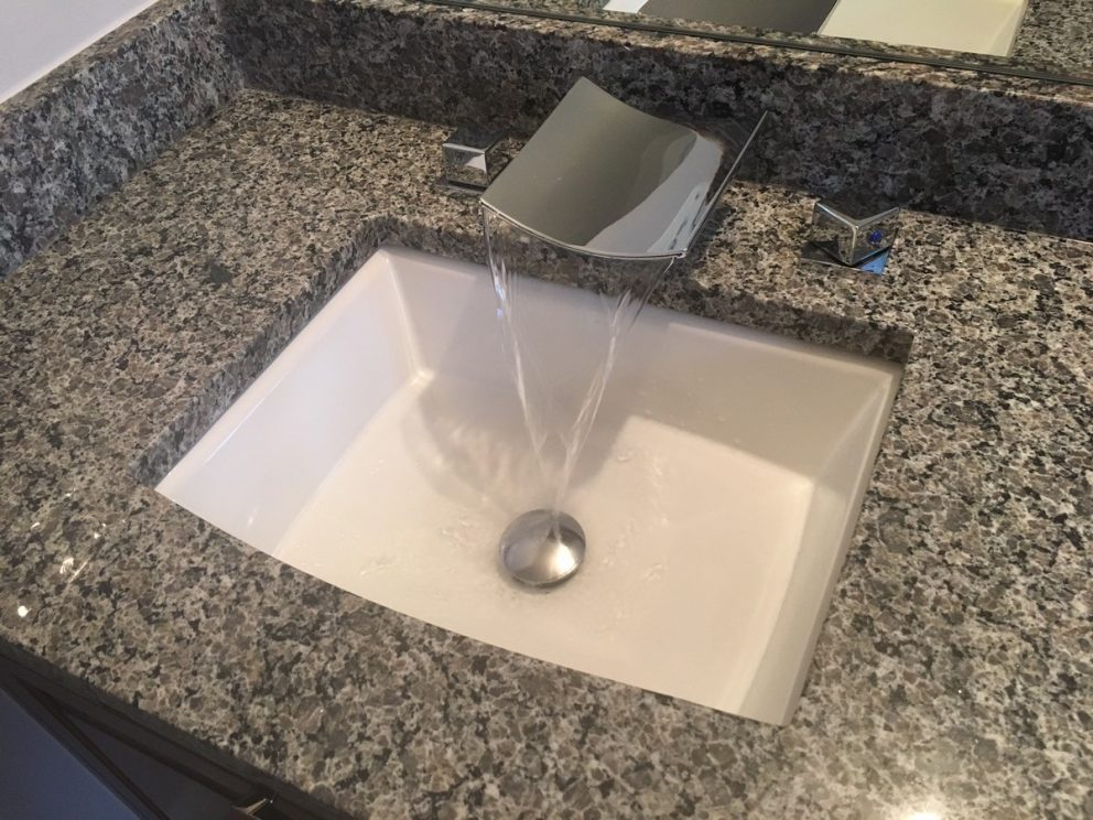 Bathroom sink featuring a waterfall faucet into ceramic sink with granite counter top