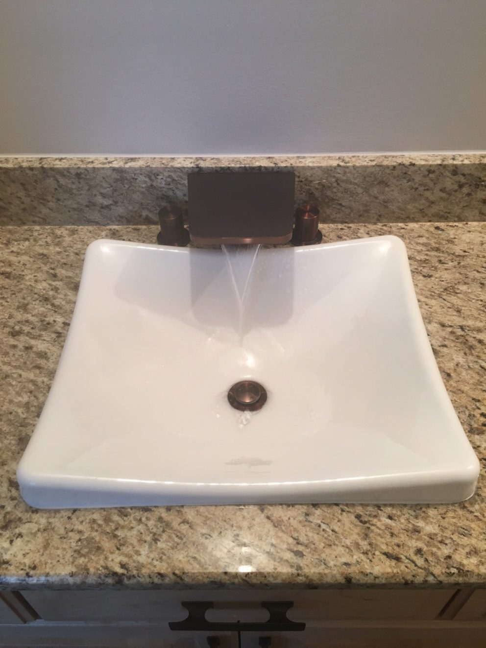bathroom sink with a cascade faucet into ceramic sink