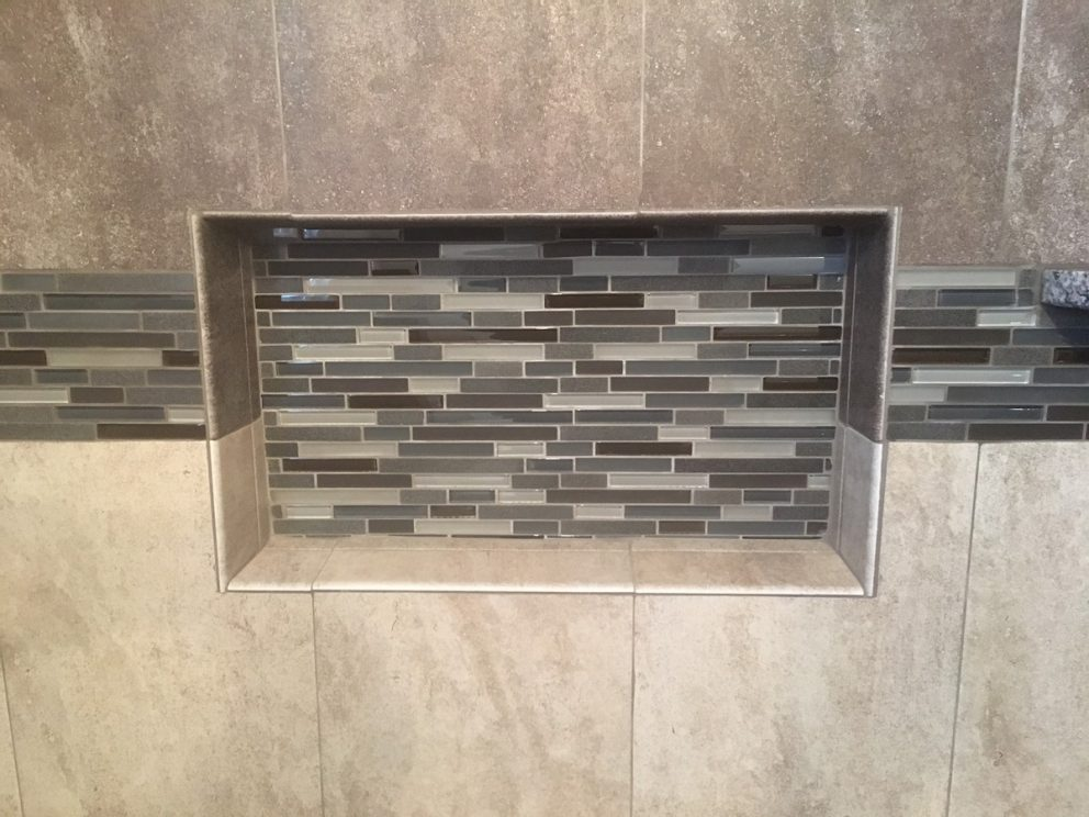 Closeup of custom shower nich tiled with accent tile