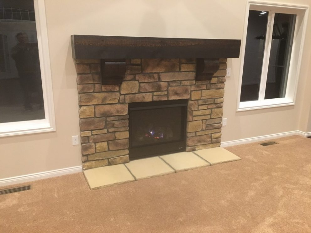 Fireplace surrounded in brick with tile footing and wooden mantel