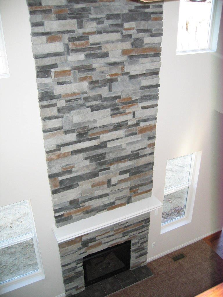 Fireplace surrounded with cut stone that continues to the ceiling