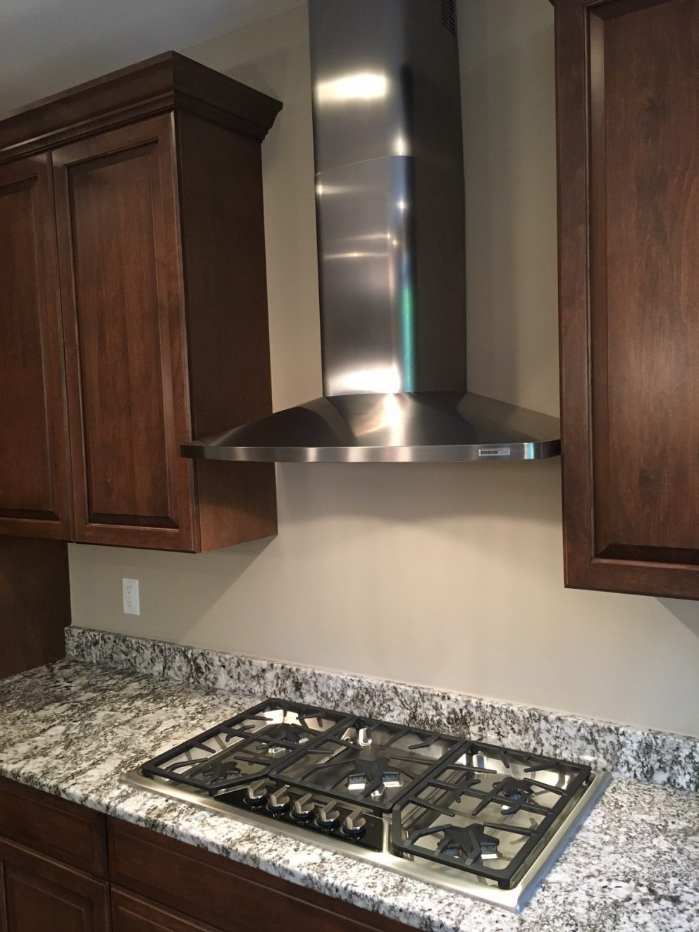 Gas cook top in granite counter top with stainless steel hood vent
