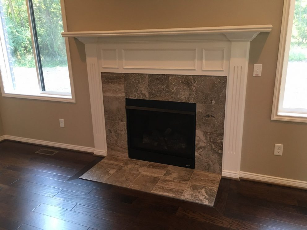 Great room fireplace with tile border and decorative mantel