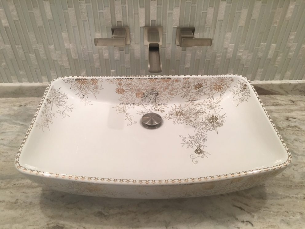 hand painted sink with faucet built into tile back wall