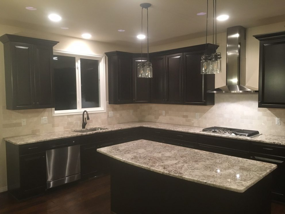 Kitchen featuring dark mocha cabinetry, granite counter tops, stainless steel hood vent built, and built in cook top