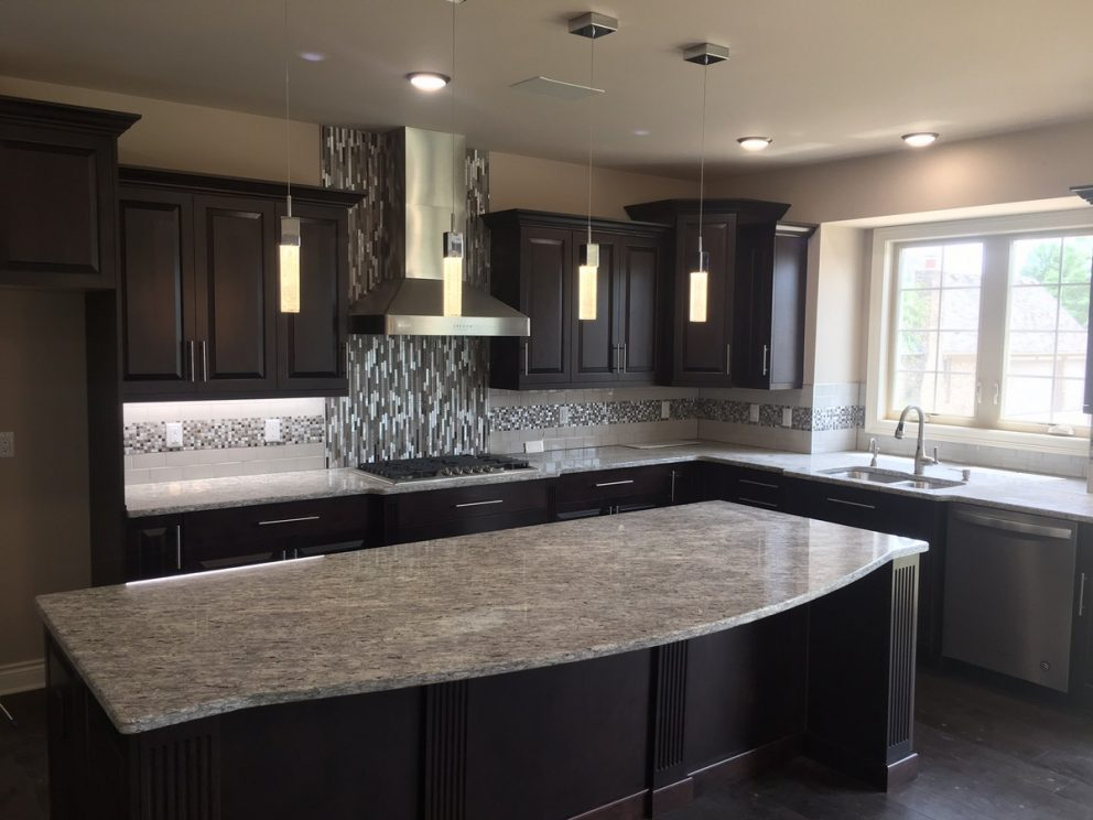 kitchen featuring granite countertops, tile backsplash, and mocha cabinetry