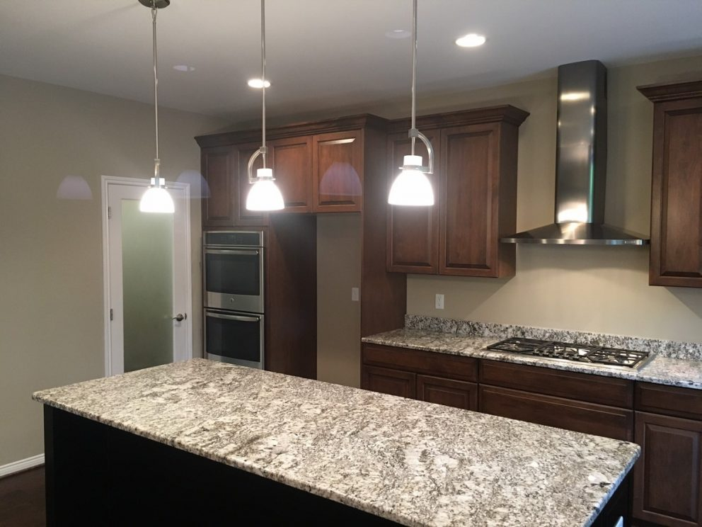Kitchen lights hung over a granite counter top island