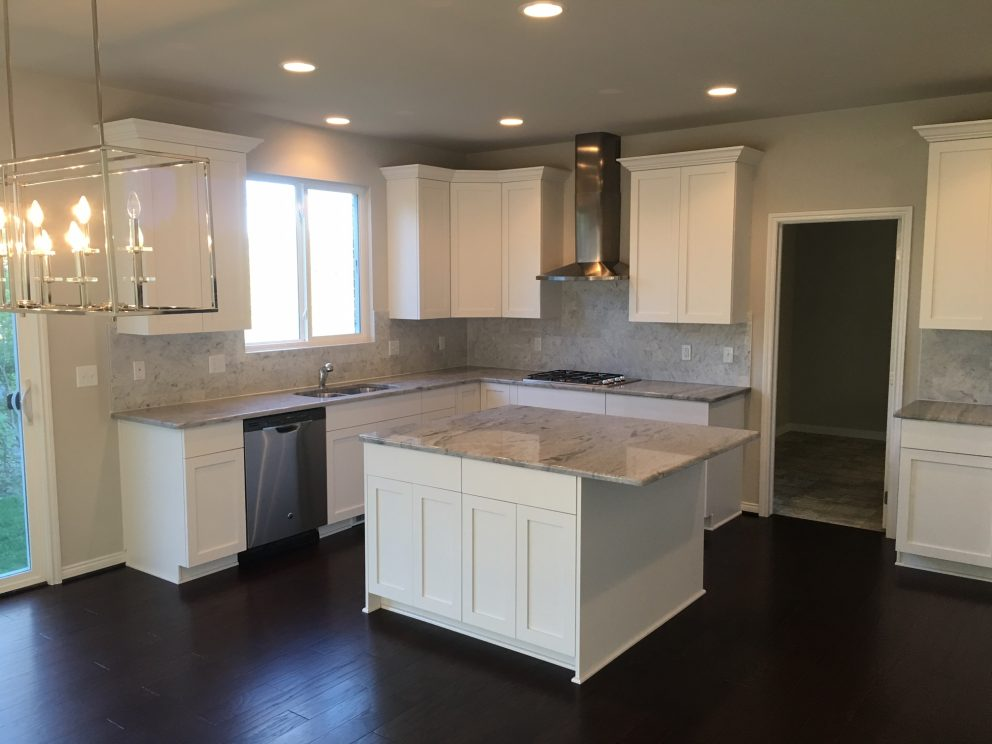 Kitchen with white painted cabinets featuring shaker doors, contrast with a dark hardwood floor