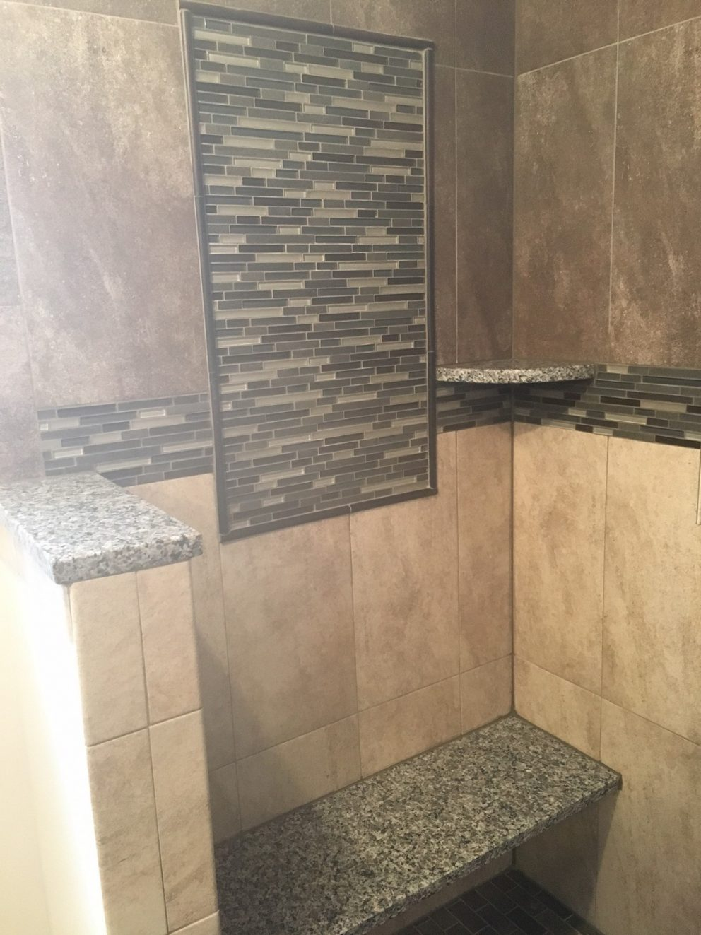 Master bath shower with custom granite bench and accent tiling