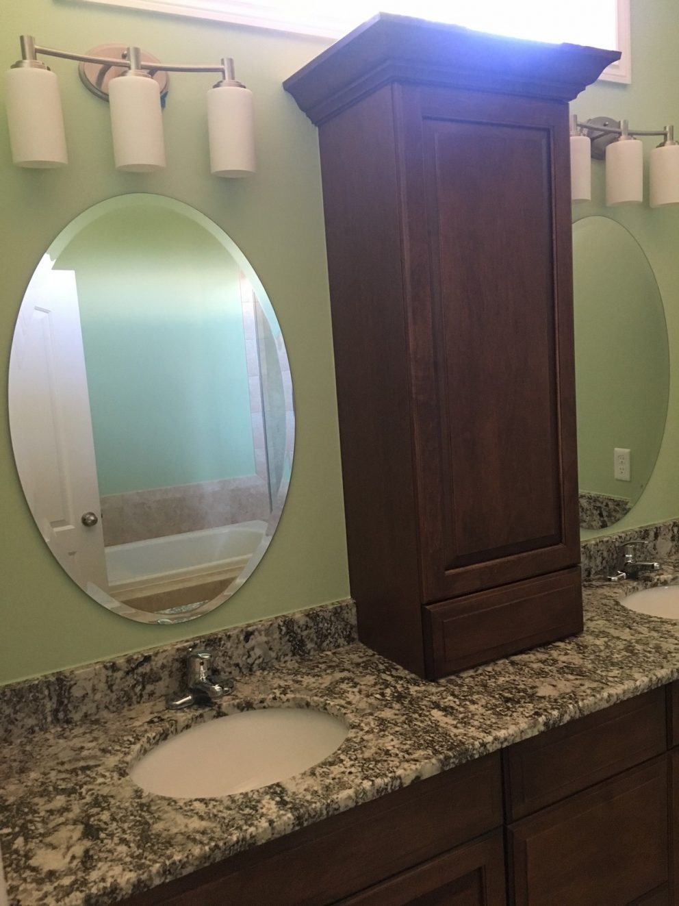 Master bath sinks with granite counter tops and a tower cabinet