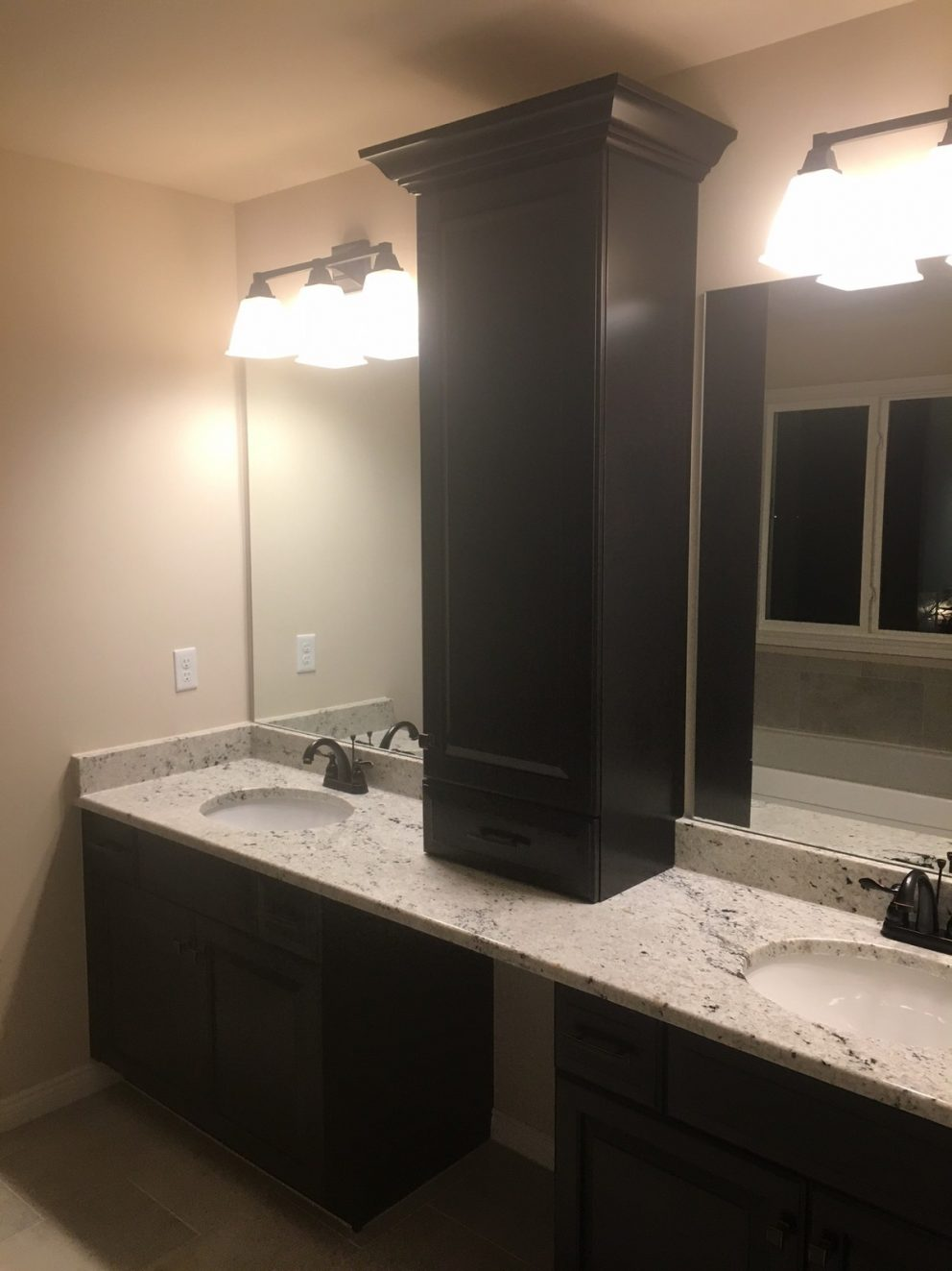 Master bath with his and her sinks and tower cabinet