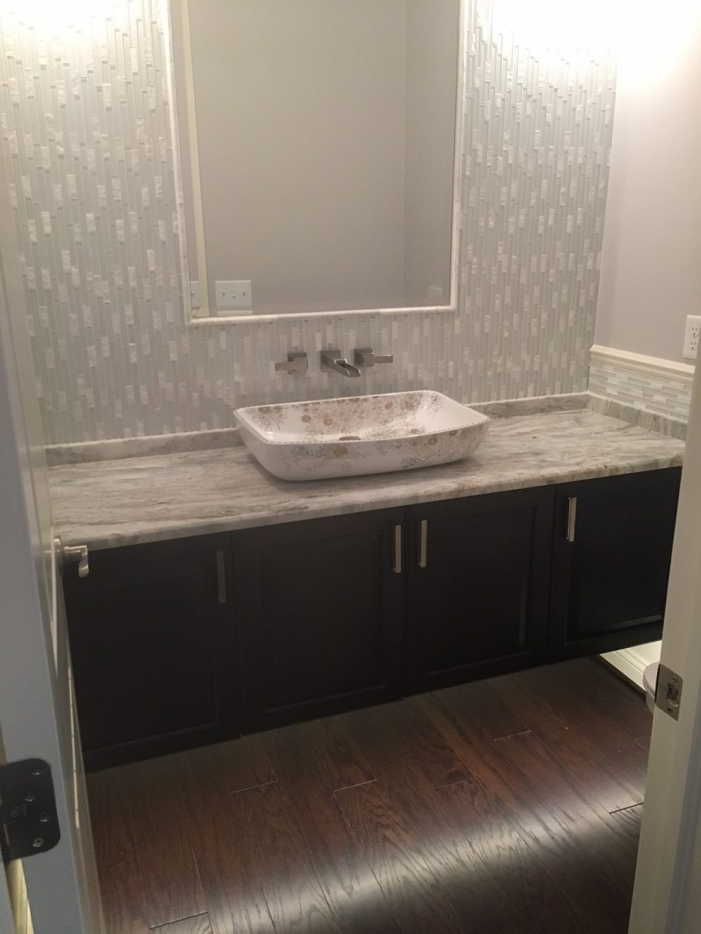 Powder room with floating vanity, mirror inlay and tile back wall