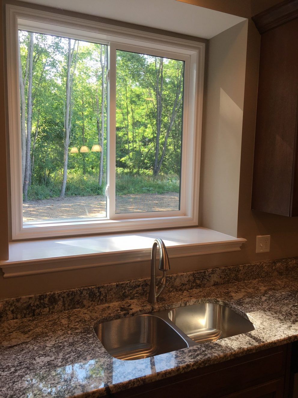 Stainless steel kitchen sink in granite counter top with bay window